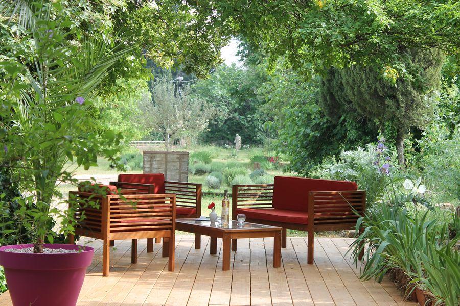 terrasse en bois du gîte, salon de jardin, bouteille de rosé posée sur la table